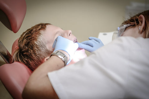 Dentist examining a little boy's teeth, for AutoBrush
