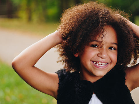 Smiling girl with curly hair posing