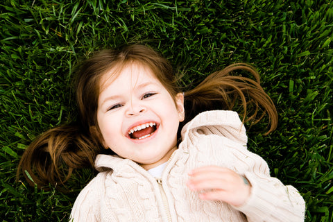 Girl lying on the grass smiling, for AutoBrush