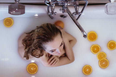 Woman in a bath tub with floating oranges, for AutoBrush