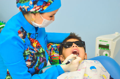 A dentist examining a boy wearing shades, for AutoBrush