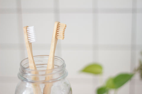 Two wooden toothbrushes placed in a jar with white tiles background, for AutoBrush