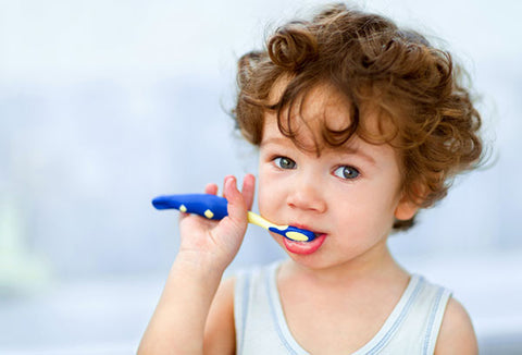Toddler brushing teeth using a blue toothbrush, for AutoBrush