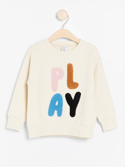 Beige sweatshirt med frotté applikation