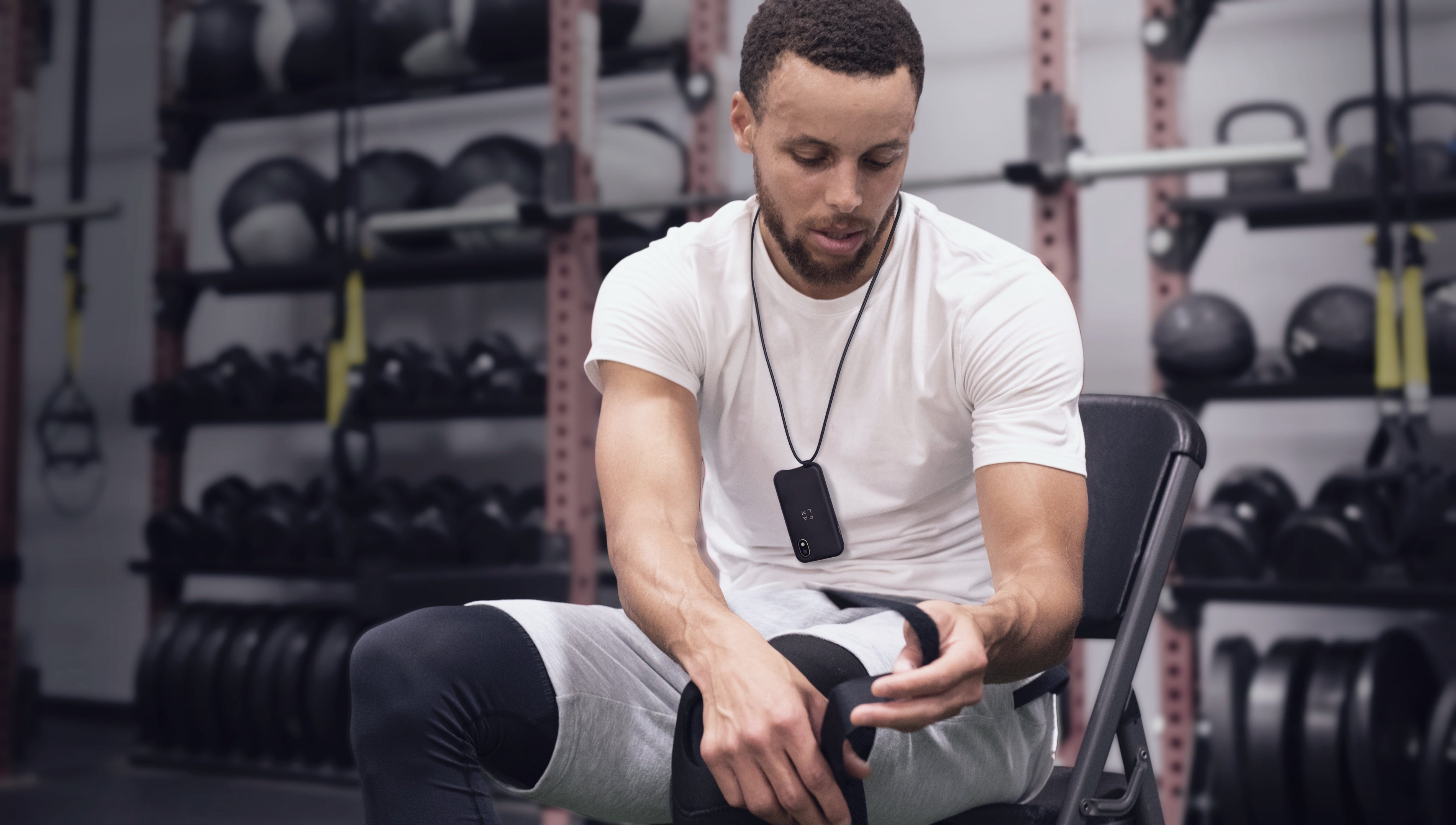 Stephen Curry wears a Palm smartphone in a lanyard case
