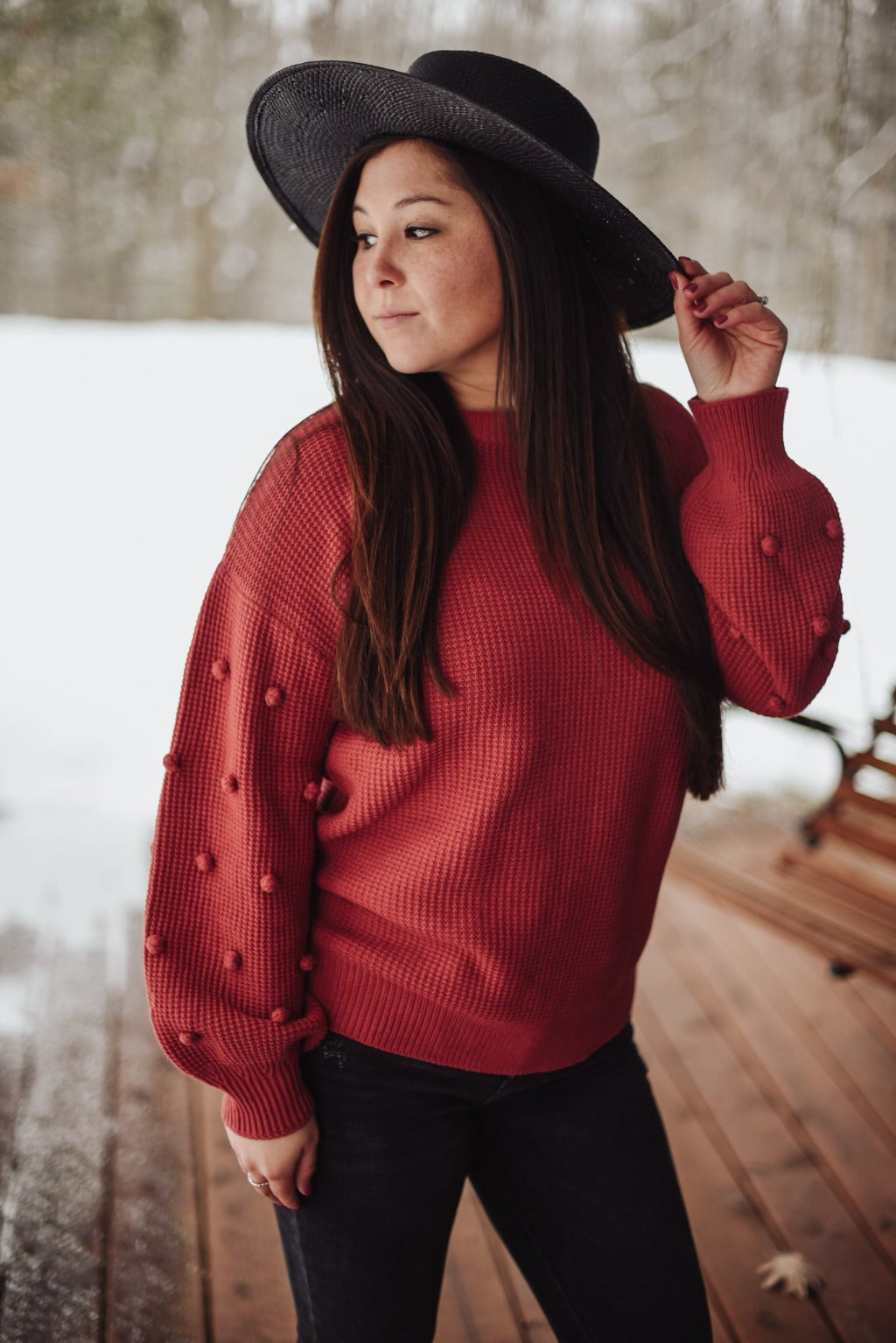 Woman wearing a marsala color sweater.