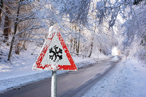 A snowy road with a frosted over road sign.