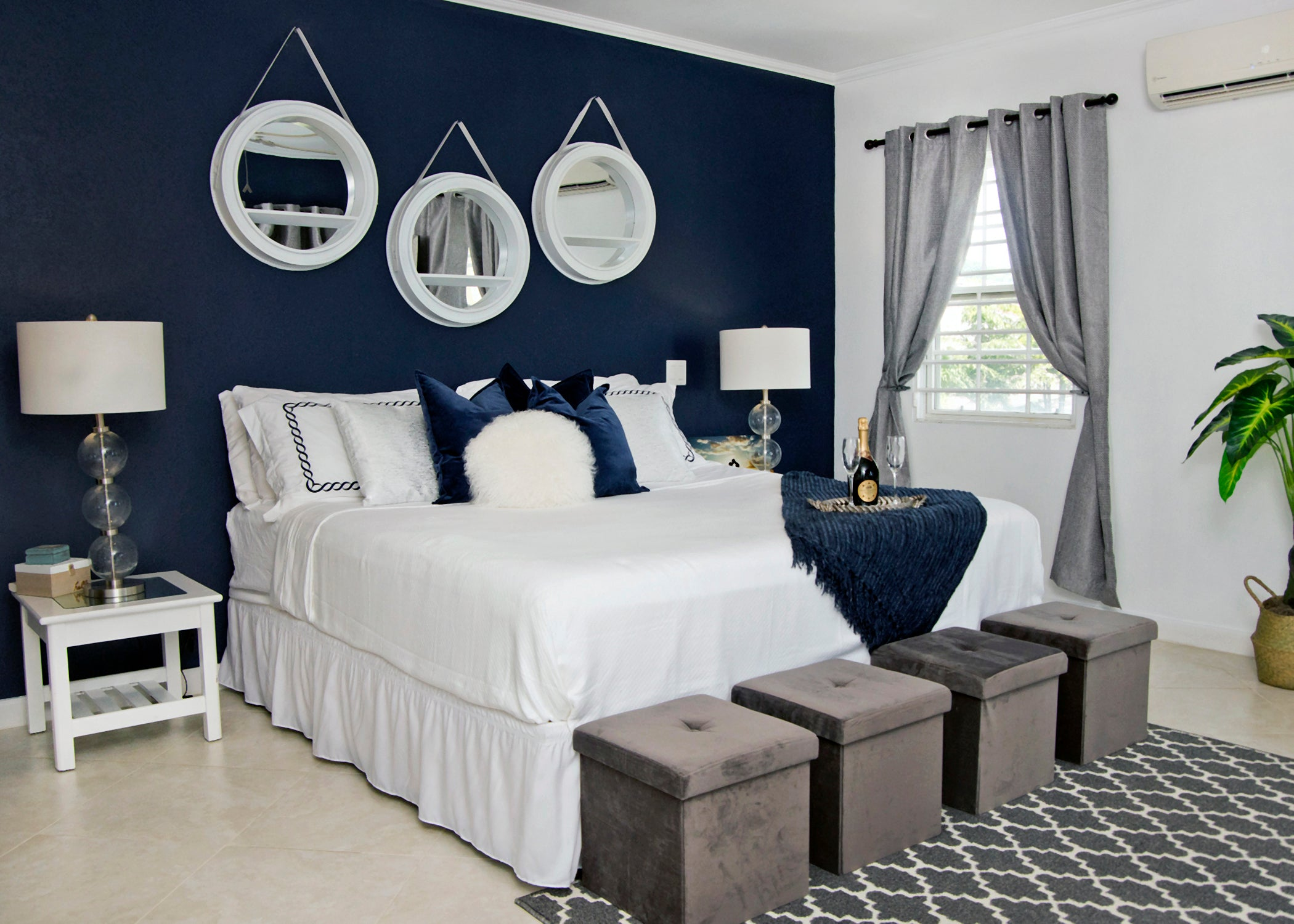 Bedroom with navy accent wall, and neutral decor. Clam, sophisticated, and elegant design by a Harris Paints' Colourcentre staff member