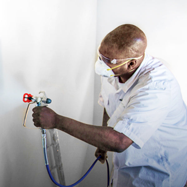 A man using a Graco paint sprayer on a wall. Graco Spray Equipment is available at Harris Paints in the Caribbean.