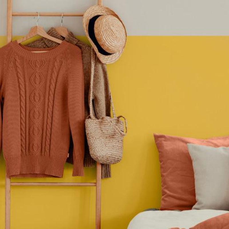 bedroom wall painted with 0864 Lioness a fun yelllow and also the Harris Paints Colour of the Year for 2020, accented with a rusty orange cushions