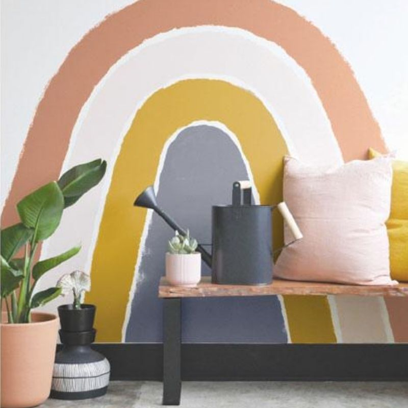 wall painted with a deep rose gold color, light pink, deep yellow, and purple rainbow. explore the paint colour trends of 2020 at Harris Paints