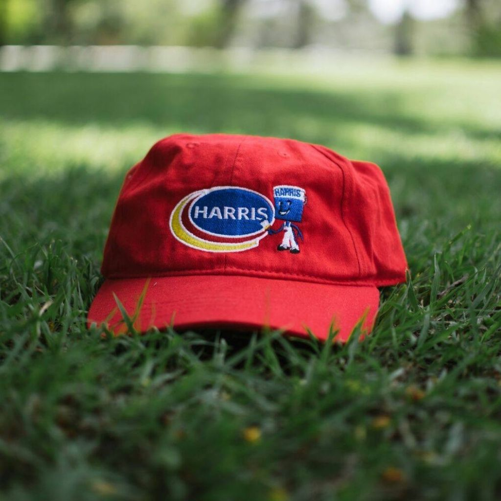 red hat with Harris Paints logo displayed in the grass