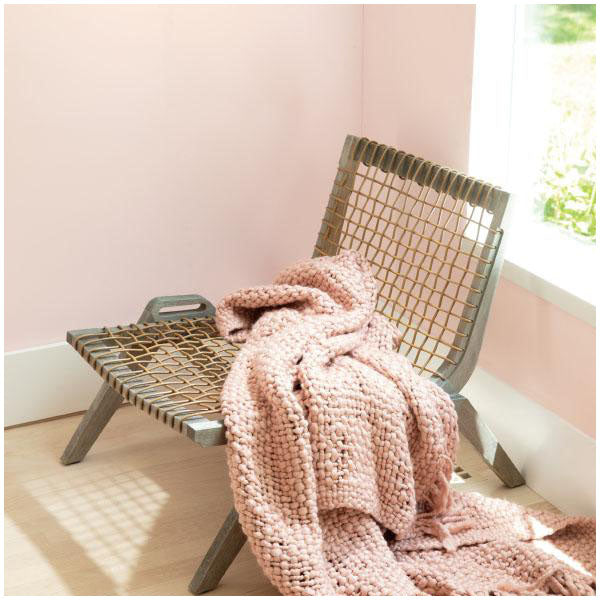 Benjamin Moore's Color of the Year 2020 First Light in a living room with natural wood chair and pink knitted blanket