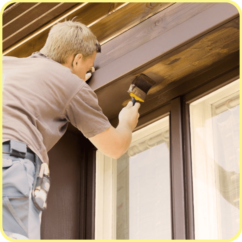 home owner staining the exterior window trim of his home