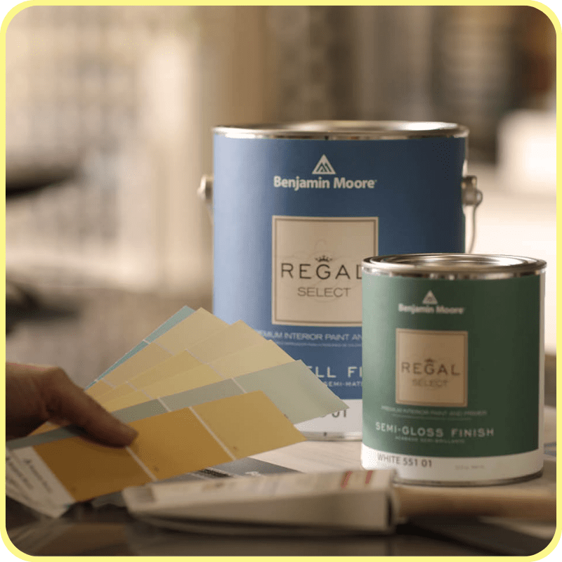Gallon of Benjamin Moore Regal paint, and a quart of Benjamin Moore paint on a paint counter next to a Wooster paint brush and yellow & green paint swatches.