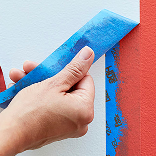 Peeling off blue 3M painter's tape from a wall.