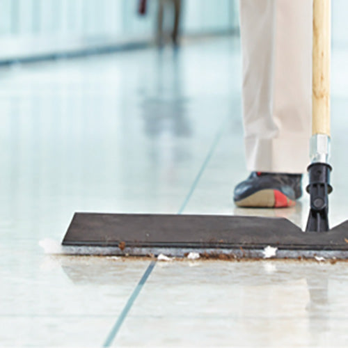 A large broom cleaning an industrial floor.