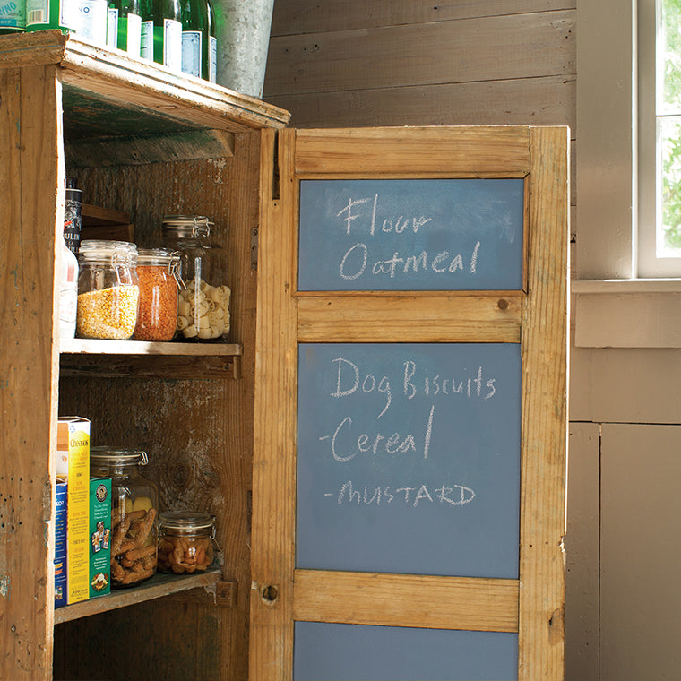 A pantry cabinet with an open door that has been painted with Benjamin Moore's chalkboard paint on the inside, with a list of food items written in chalk on the door.
