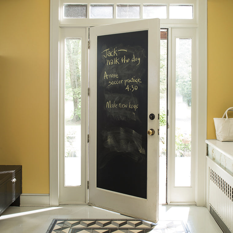 The back of a front door that has been painted black using Benjamin Moore's chalkboard paint, with a to do list written in yellow chalk.