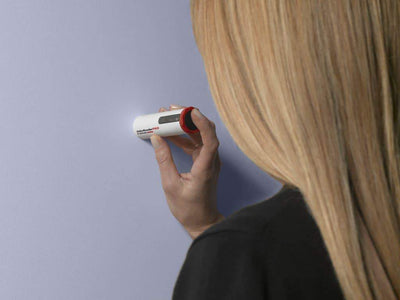 A woman using the Datacolor ColorReaderPRO on a light purple wall to determine the closest paint color match, a professional color reading device available at John Boyle Decorating Centers in Connecticut.