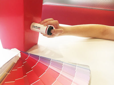 A person using the Datacolor Color Reader on a red object to determine the closest paint color match, available at John Boyle Decorating Centers in Connecticut.