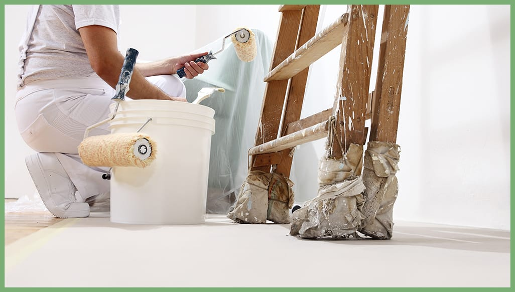A painting contractor with paint roller frames, a bucket and ladder.