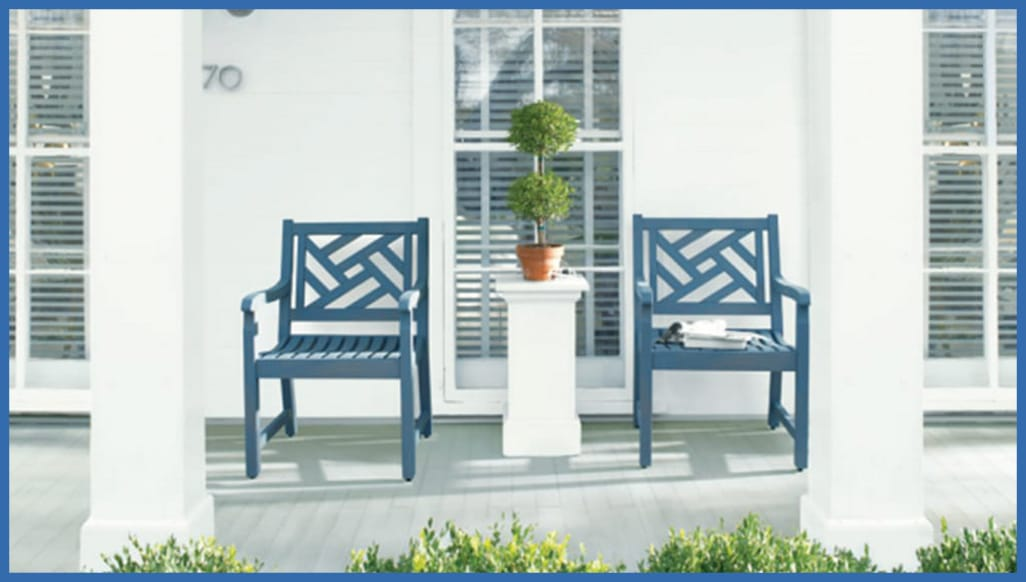 Two blue painted chairs on a porch in front of a white house painted with Benjamin Moore paint.