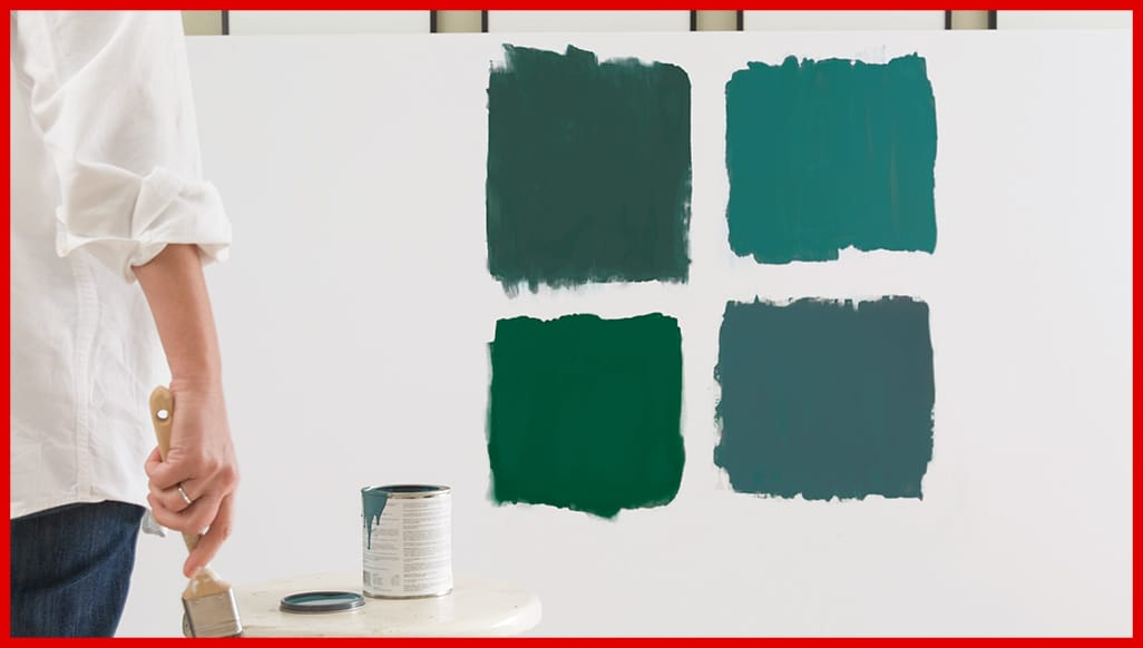 Four Benjamin Moore green paint color samples painted on a wall.