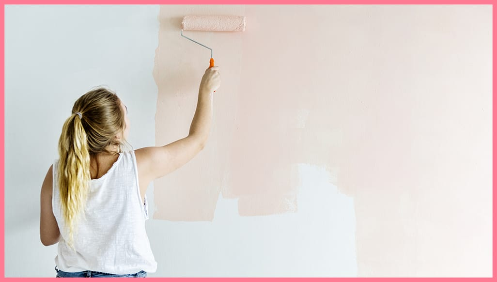 A woman using a paint roller to paint a wall light pink.