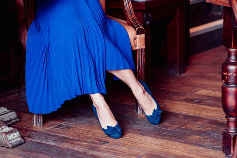 woman in cafe in blue pleated skirt and blue suede shoes
