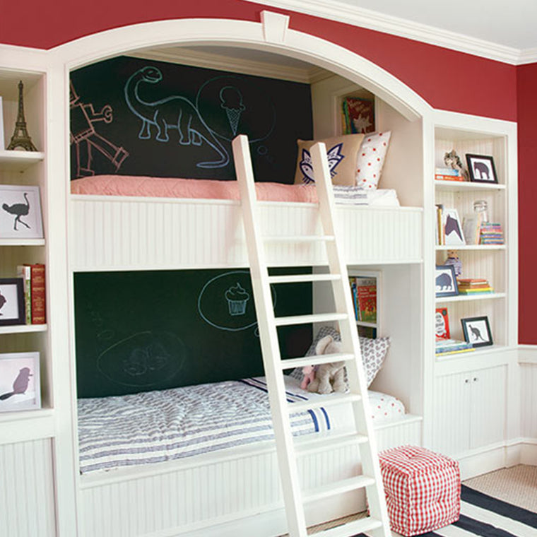 A child's bedroom showing bunk beds in the wall, with the back wall painted with Benjamin Moore's Chalkboard paint, showing dinosaurs and a cupcake drawn in chalk.