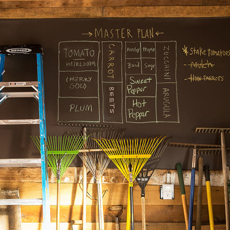 A garage wall that has been painted with Benjamin Moore's Chalkboard Paint, showing a list of vegetables to be planted in a garden.