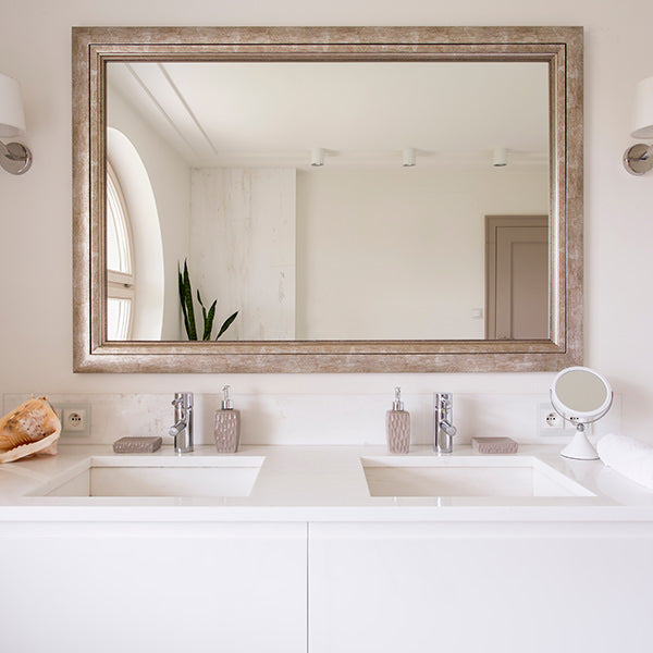 A bathroom with a white vanity and double sink, with a large mirror hanging above, in a gold frame.