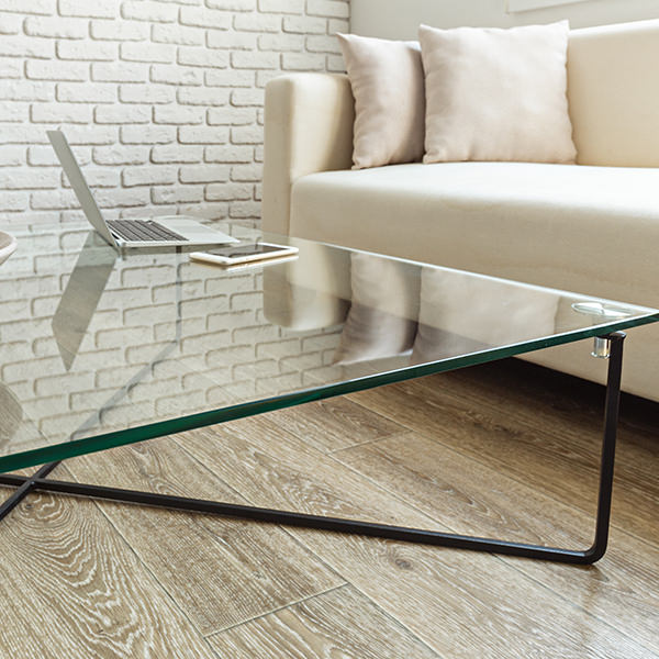 A coffee table with a glass top, in front of a beige couch on brown hardwood flooring.