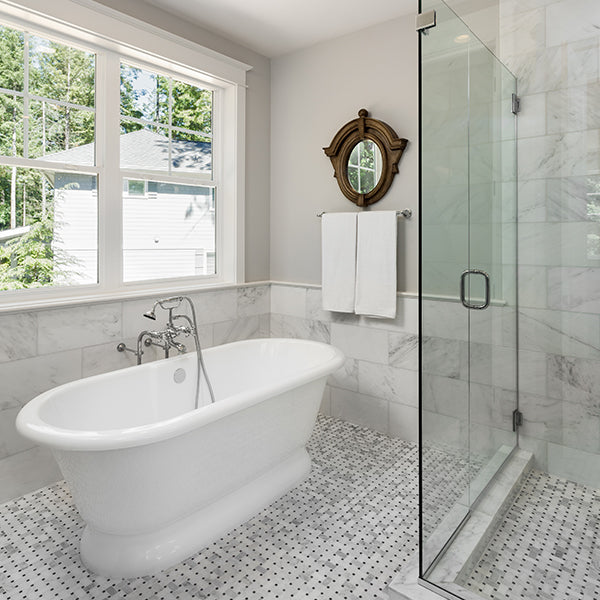 A bathroom with a large white bath tub, grey and white floor tile and a shower with glass doors.