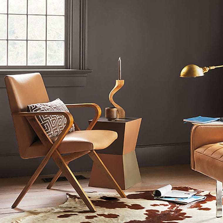 Benjamin Moore Colour Trends 2021 Silhouette (AF-655) Living Room scene with brown padded chair, side table with a candle holder and a cow coloured rug