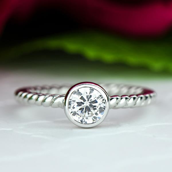 0.25 Carat Round Cut Bezel Infinity Engagement Ring in White Gold over Sterling Silver