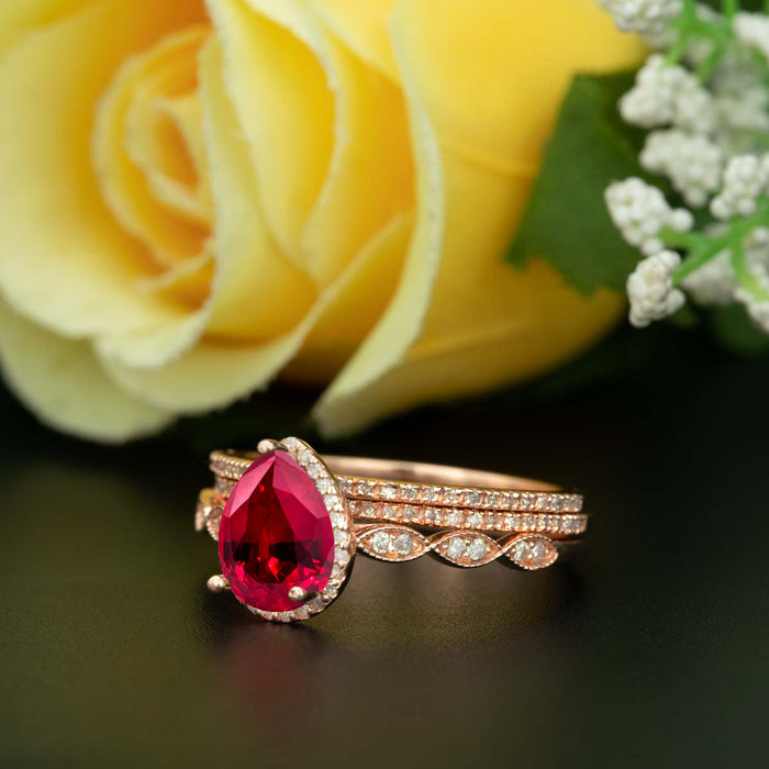 2 Carat Pear Cut Halo Ruby and Diamond Ring with 2 Classic Wedding Bands in 9k Rose Gold
