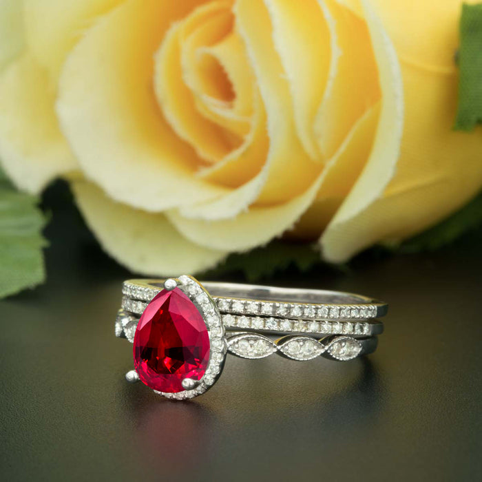 2 Carat Pear Cut Halo Ruby and Diamond Ring with 2 Classic Wedding Bands in 9k White Gold