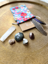 example of stones and feathers with floral gem pouch