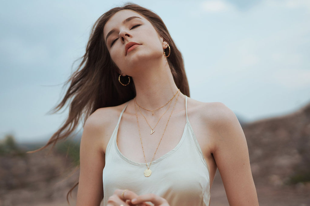 model with layered gold plated necklace and gold plated large hoops earrings
