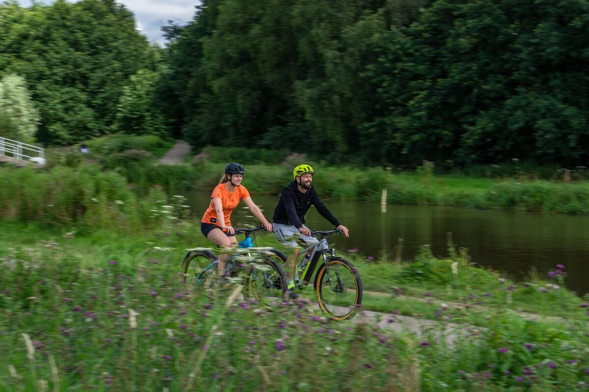 Couple showing the electric bike health benefits or riding an e-bike through the country