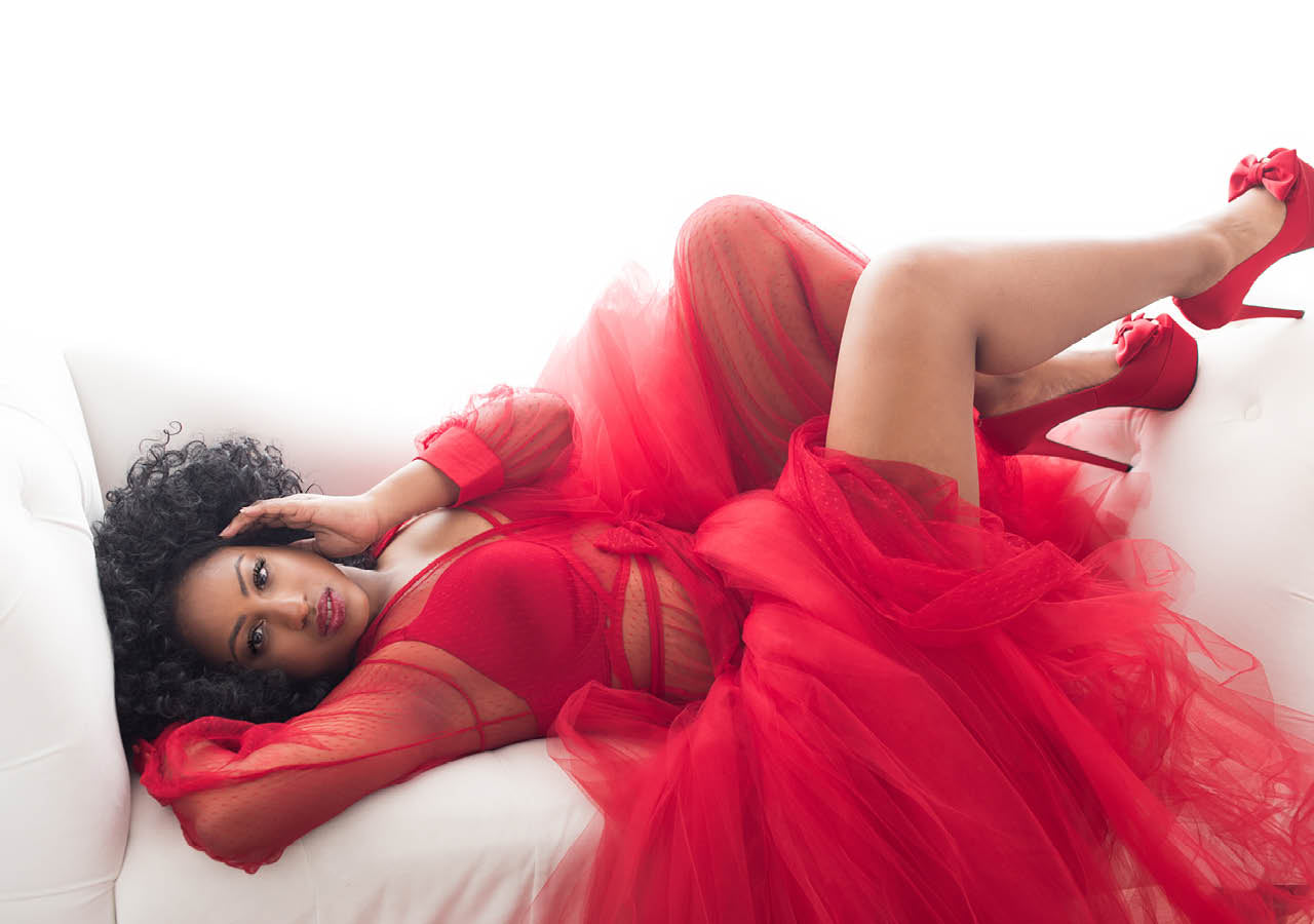 Woman laying down wearing a red dress and heels