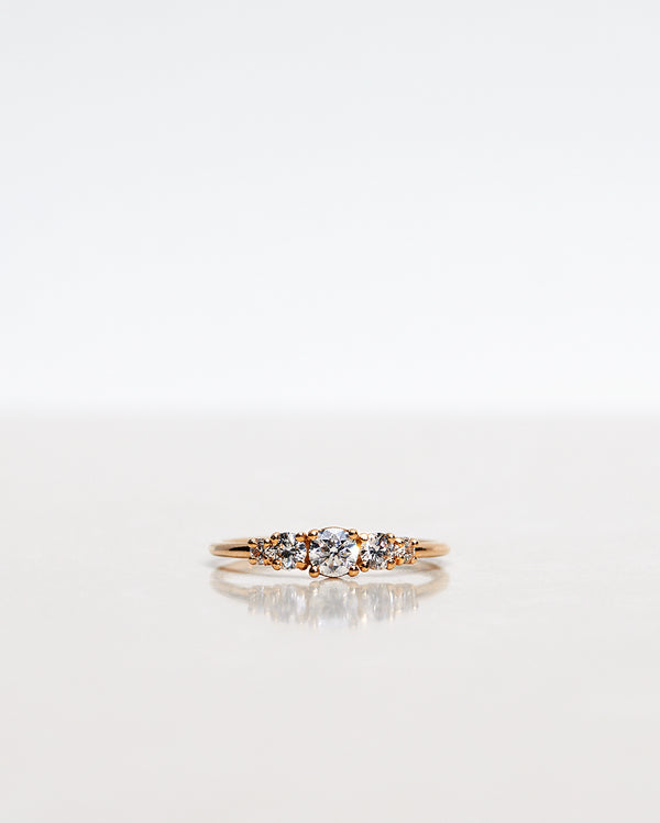 Mumbaistockholm Fine Jewelry Ring: Elise Ring in 18K yellow gold with five white, conflict-free diamonds. The center diamond is 0.25 CT, and on each side are two 0.11 CT diamonds, and two 0.04 CT diamonds. Pictured from the front.