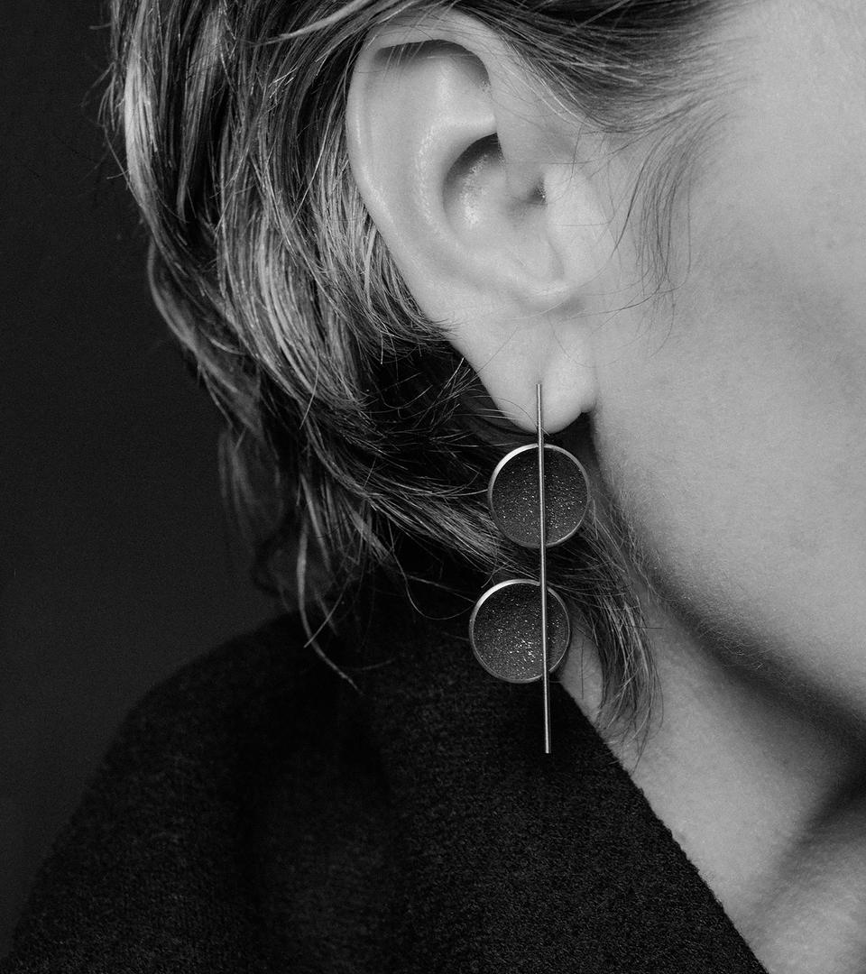 Model wears double domed earrings in stainless steel set with diamond dust and concrete.