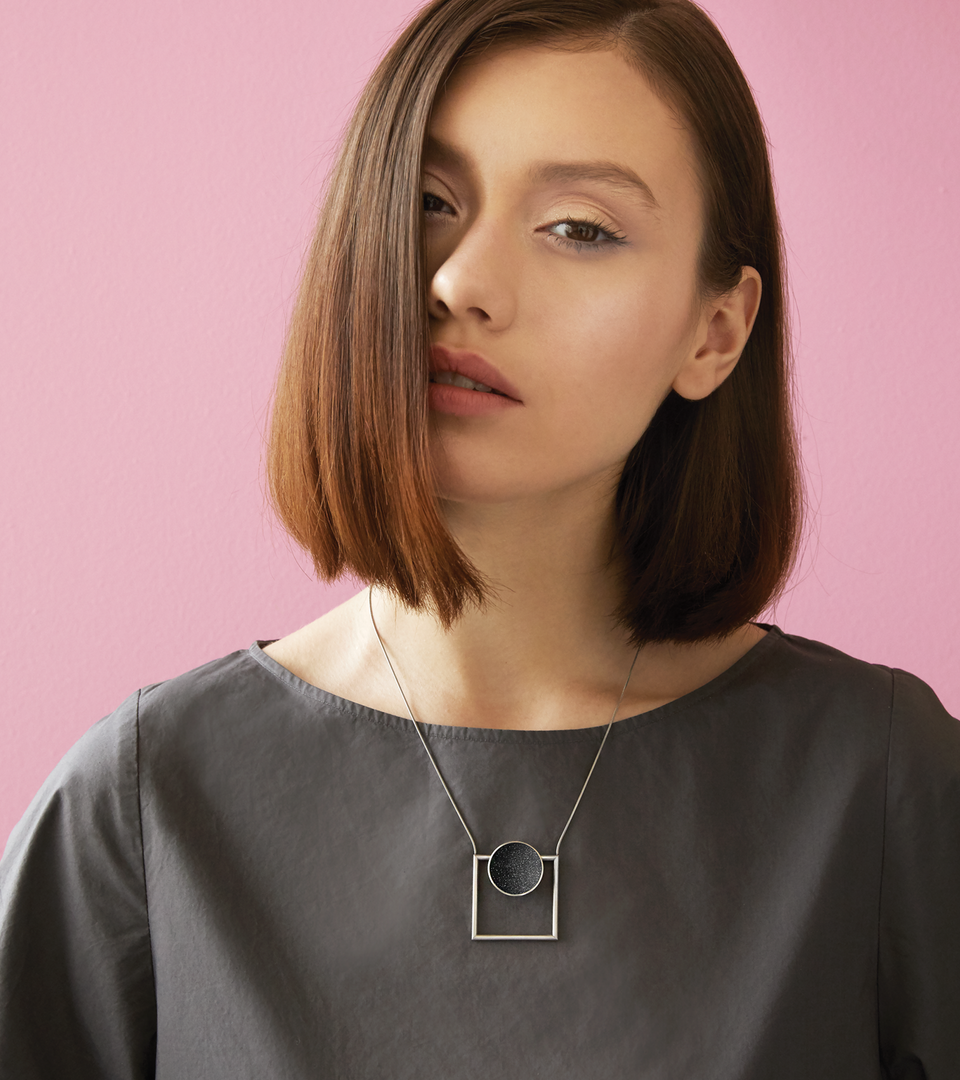 This Contemporary necklace combines the geometry of a large stainless steel dome lined with the sparkle of diamond dust encrusted concrete suspended onto a minimalist steel square frame.