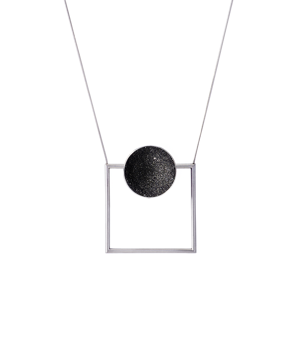 This Bauhaus inspired geometric necklace features a large stainless steel dome lined with the sparkle of diamond dust encrusted concrete and suspended onto steel square frame.