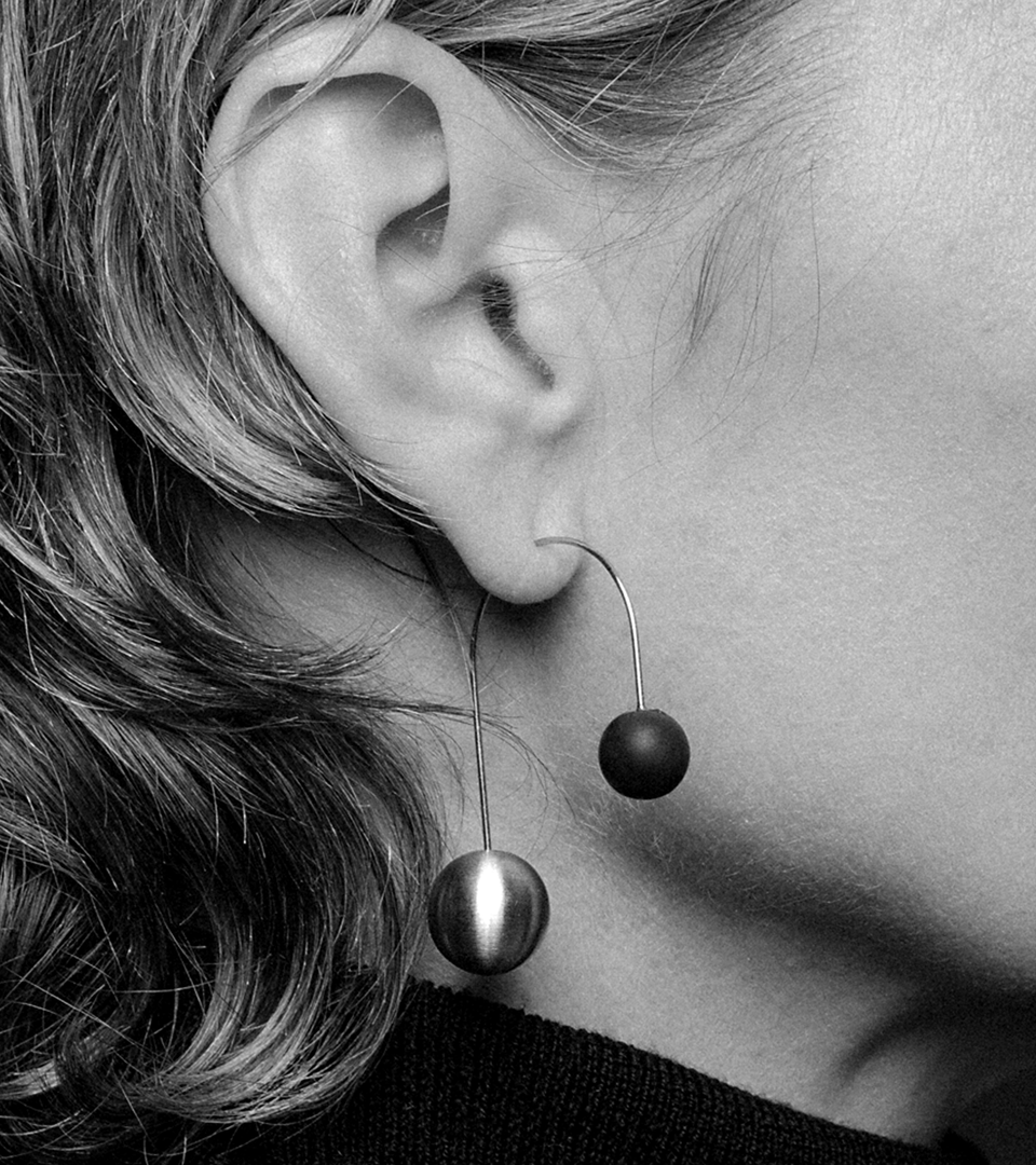Model wears statement earrings architecturally balancing stainless steel and concrete spheres.