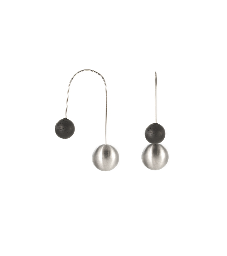 Statement earrings architecturally balancing stainless steel and concrete spheres.