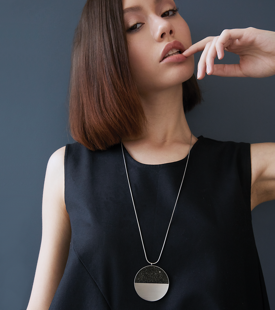 Statement necklace balancing stainless steel with diamond dust infused blackened concrete.